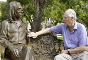 FILE - In this Oct. 30, 2002 file photo, Beatles producer George Martin touches a statue of John Lennon in a park in the Vedado neighborhood of Havana, during his visit to Cuba. (AP Photo/Cristobal Herrera, File)